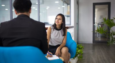 Portrait of smiling hr manager having interview with candidate. Young Caucasian businesswoman having meeting with businessman in lobby and writing after him. Meeting and job interview concept
